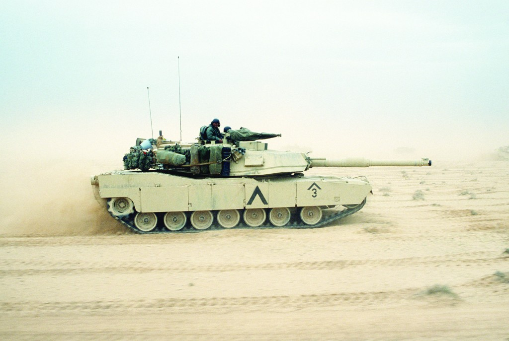 An M-1A1 Abrams main battle tank of the 3rd Brigade, 1st Armored Division, 7th Corps moves across the desert in northern Kuwait during Operation Desert Storm.