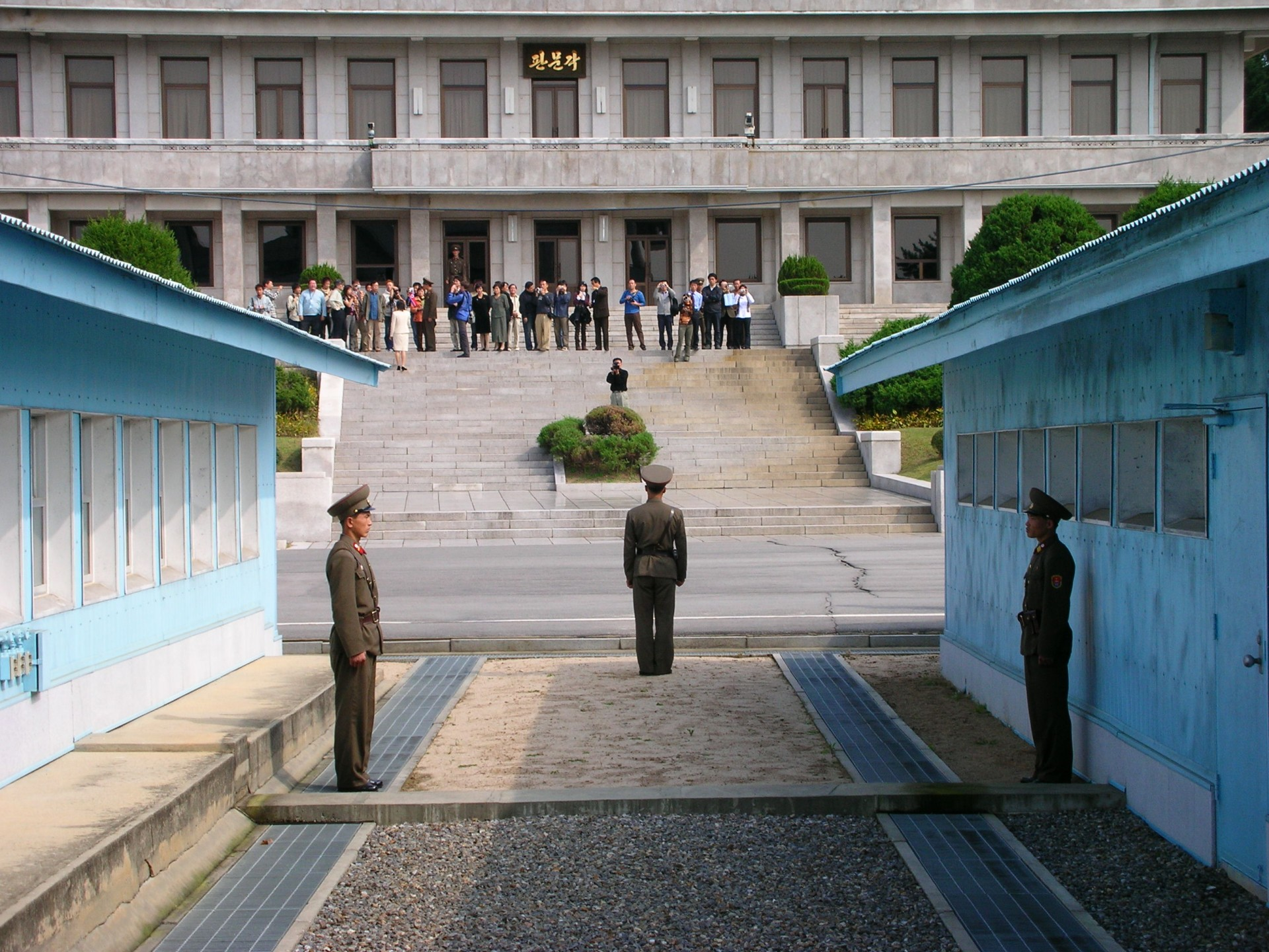 Soldiers from the Korean People's Army (KPA) stand guard at the Military Demarcation Line inside the Joint Security Area (JSA) in July 2005.  On 23 November 1984, Vasilii Matuzok, a translator working at the Soviet embassy in Pyongyang, North Korea, stepped across the concrete blocks to freedom, sparking a firefight.  (Author's collection)